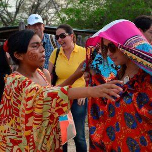 mujres luen visotsas mantas guajiras o mantas wayuu. Estas son el atuendo típico de las mujeres de la cultura indígena wayuu. Lucen vestidos multicolores. los rostros de las mujeres lucen unos trazos que las distinguen dentros de las demás mujeres en la ranchería. Nativa de la etnia wayuu y mujer arijuna en esta imagen.