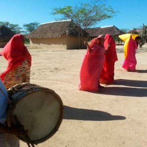 """indígena toca el tambor conocido como """"kasha"""", con el que hace un llamado a la Yonna. Esta es una danza ejecutada dentro de los rituales indígenas en agradecimiento a Dios """"Maleywa"""" por favores recibidos, por la lluvia y por la abundancia de la cosecha. Cuando una mujer pasa de jimoto a majayut, es decir de señorita a mujer se realiza una yonna para que ls comuidades vecinas sientan ell sonido del tambor y sepan que están invitados a presenciar la salida del encierro de una nueva mujer."""